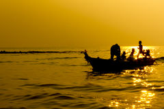 现出轮廓在小船的渔夫家庭在日落 库存图片