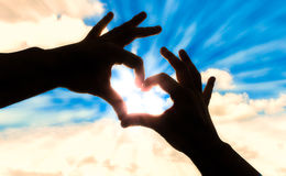 现出轮廓在心脏形状和蓝天的手 免版税库存图片