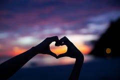 现出轮廓在心脏形状的手与在的日落 免版税库存照片