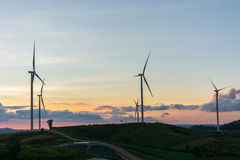 现出轮廓在日落夏天风景的造风机涡轮我 免版税图库摄影