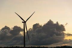 现出轮廓在日落夏天风景的造风机涡轮我 库存图片