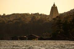 现出轮廓在晚上日落天空的金黄chedi Buddhakhaya (星期一)与河和船库在sangkhlaburi 库存照片