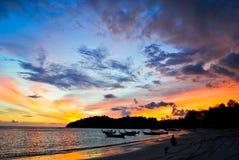 现出轮廓在海滩的小船反对日落 免版税库存照片