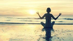 现出轮廓在海滩的少妇实践的瑜伽在日落 免版税库存图片