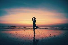 现出轮廓在海滩的少妇实践的瑜伽 免版税库存照片