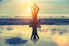 现出轮廓在海滩的年轻女性实践的瑜伽在惊人的日落 自然 免版税库存图片