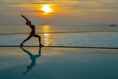 现出轮廓在游泳池和海滩的少妇实践的瑜伽在日落 免版税库存图片