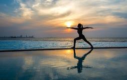 现出轮廓在游泳池和海滩的少妇实践的瑜伽在日落 库存图片