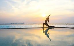 现出轮廓在游泳池的少妇实践的瑜伽 免版税库存图片
