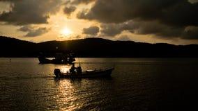 现出轮廓在湖的一条小船 免版税库存照片