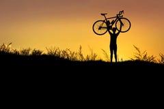 现出轮廓在行动举的自行车的人立场在他的有日落的头上 库存图片