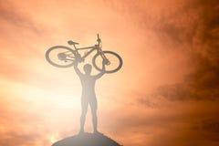 现出轮廓在行动举的自行车的人立场 免版税库存照片