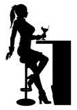现出轮廓坐在与鸡尾酒的酒吧的妇女 免版税库存图片