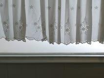 现出轮廓垂悬在窗口和墙壁有阳光半透明后面的,装饰内部室的白色鞋带缎帷幕 免版税库存照片