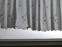 现出轮廓垂悬在窗口jamp与阳光半透明后面,装饰内部上的窗口的白色鞋带缎帷幕 库存照片