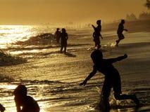 现出轮廓夏天人获得乐趣在海滩日落 库存图片