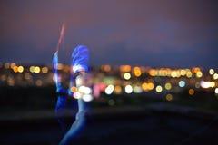 现出轮廓夜城市背景的女孩  免版税库存图片