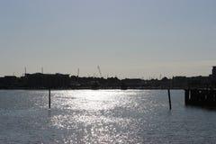 现出轮廓大厦的闪烁太阳的港口 免版税库存图片