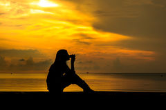 现出轮廓妇女饮用的咖啡在海滩附近在日落 免版税库存照片