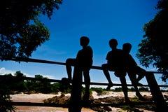 现出轮廓小男孩坐篱芭在Khone Phapheng水 免版税库存照片