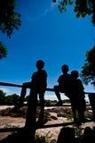 现出轮廓小男孩坐篱芭在Khone Phapheng水 图库摄影