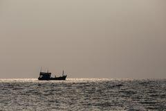 现出轮廓小船和日落在海水 免版税库存照片