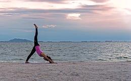 现出轮廓少妇行使重要在海滩思考和实践的瑜伽球在日落的生活方式 免版税库存图片