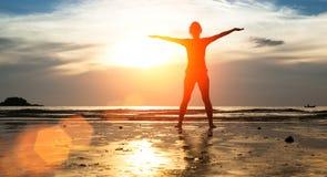 现出轮廓少妇,在海滩的锻炼在日落 愉快 免版税图库摄影