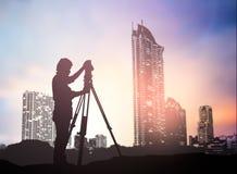 现出轮廓工作在迷离的一个建筑工地的勘测工程师 图库摄影