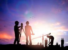 现出轮廓工作在迷离的一个建筑工地的勘测工程师 免版税库存图片