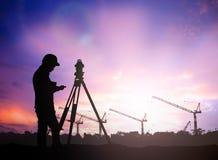 现出轮廓工作在迷离的一个建筑工地的勘测工程师 免版税库存照片