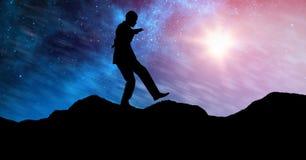 现出轮廓平衡在山的商人反对天空在晚上 免版税库存照片