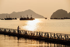 现出轮廓抓在木桥的渔夫一条鱼反对 库存图片