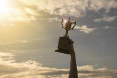 现出轮廓拿着优胜者在冠军的手战利品杯子 库存图片