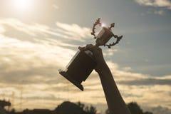 现出轮廓拿着优胜者在冠军的手战利品杯子 免版税图库摄影
