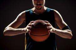 现出轮廓拿着在黑背景的观点的蓝球运动员篮子球 库存图片