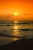 现出轮廓日落在海滩 免版税库存照片