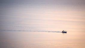 现出轮廓最小的渔场小船风帆日出在风平浪静的 库存图片