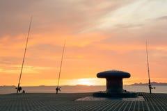 现出轮廓有日落天空的钓鱼竿在海边码头 免版税库存图片