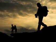 现出轮廓有照相机的旅行家和在岩石的夫妇在s 库存照片