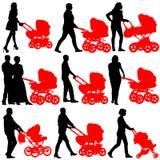 现出轮廓有婴儿车的walkings母亲 免版税库存图片