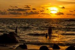 现出轮廓海滩的人在日落时间 库存图片