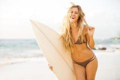 现出轮廓海滩的冲浪者女孩在日落 免版税图库摄影