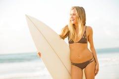 现出轮廓海滩的冲浪者女孩在日落 库存照片