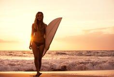 现出轮廓海滩的冲浪者女孩在日落 库存图片