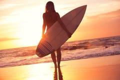 现出轮廓海滩的冲浪者女孩在日落 免版税库存图片