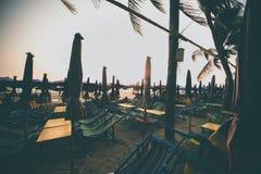 现出轮廓海滩睡椅日落在海滩的 免版税库存照片