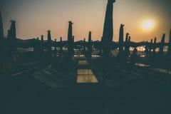 现出轮廓海滩睡椅日落在海滩的 库存照片