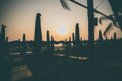 现出轮廓海滩睡椅日落在海滩的 图库摄影