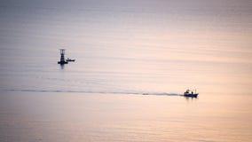 现出轮廓渔场在风平浪静的小船风帆日出有lightho的 图库摄影